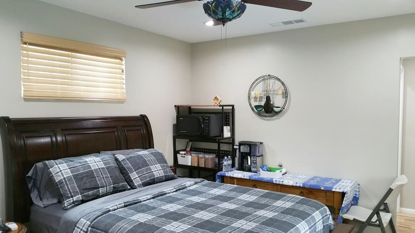 Large Bedroom with queen bed,  desk, microwave, mini fridge and coffee machine