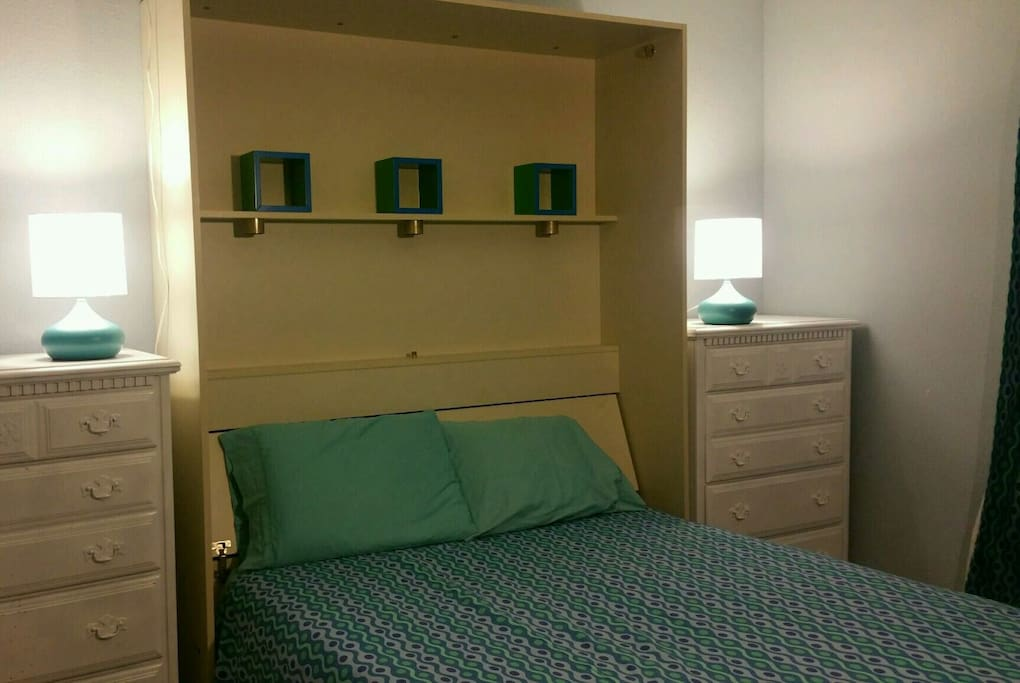 Modern Murphy bed room with comfortable Queen-sized mattress