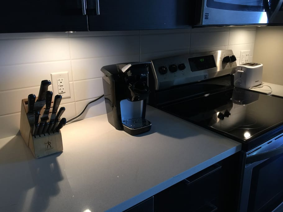 Modern kitchen with basic items to be able to cook at home including a Keurig machine, plates/cups & pans