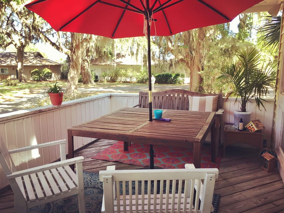 Big table under red umbrella sits 5 on big front deck area