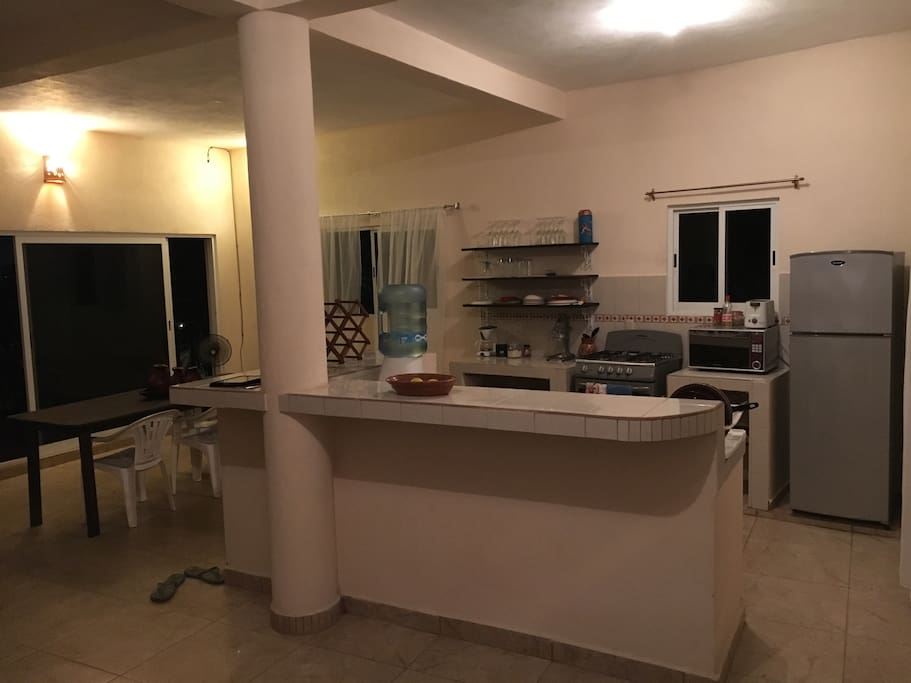 Open kitchen with refrigerator, gas stove, microwave, coffee machine, orange press, pots and pans, dishes and cutlery