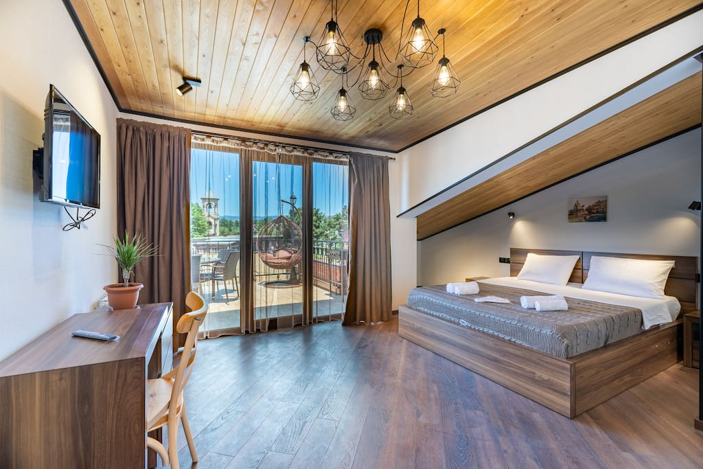 Spacious bedroom with working desk and entrance on terrace