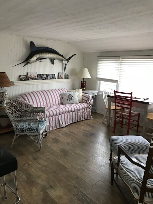 Living area - coastal charm in an ocean block 2nd floor unit with private entrance including large outside deck for eating and relaxing . Outside shower and gas grill also included .