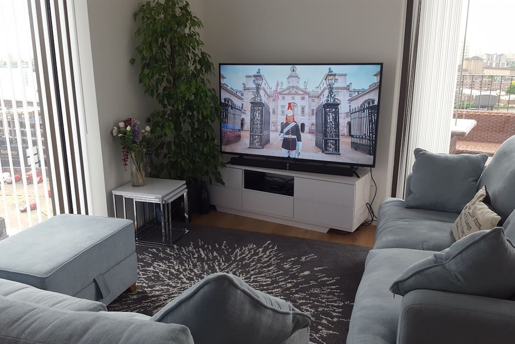 """Giant 60"""" 4K Smart TV and lounge area"""