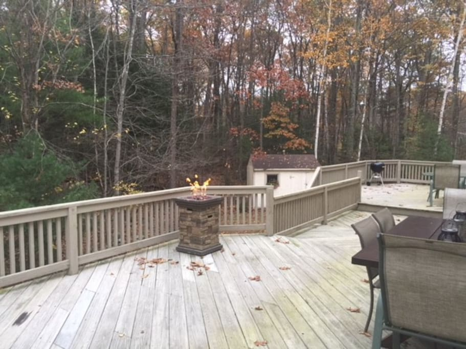 Large back deck overlooking a secluded wooded area with seating, table and charcoal grill available for use.