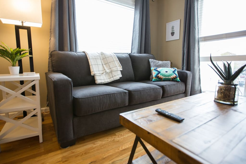 "After a great night out, relax in our stylish, comfy living room! Complete with pull-out sofas (couch pulls-out into a queen, loveseat pulls out into a twin) and a 55"" Smart TV."