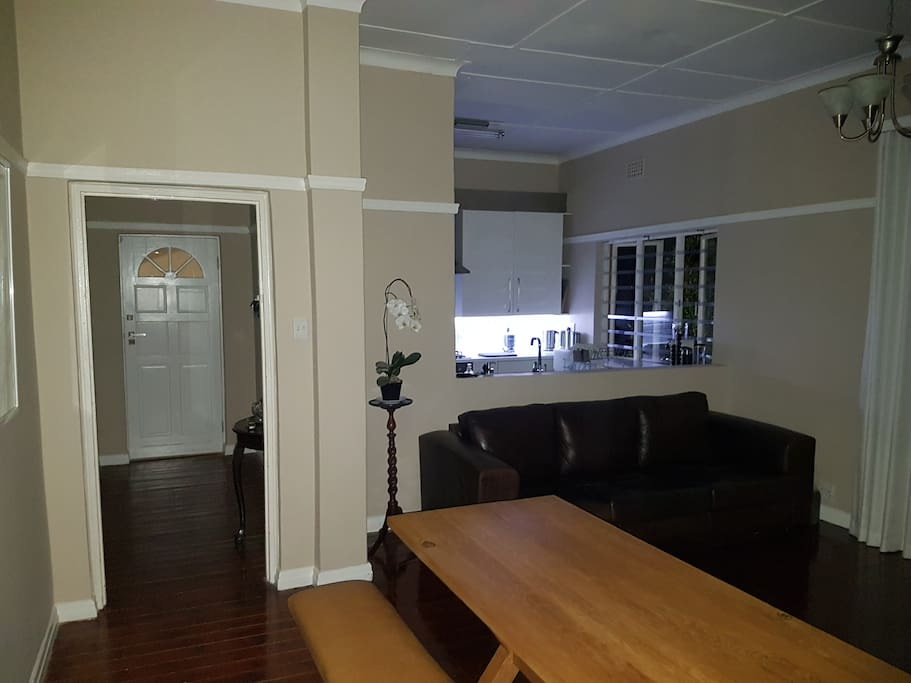 Entrance door, kitchen and lounge with 3 seater leather couch