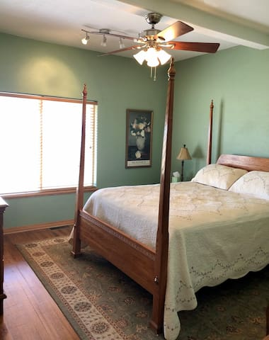 Queen size bed with ceiling fan on main level.