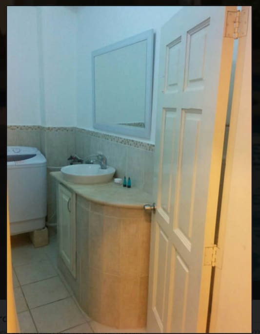 Large Bathroom, shower, toilet, sink, laundry, & bidet.
