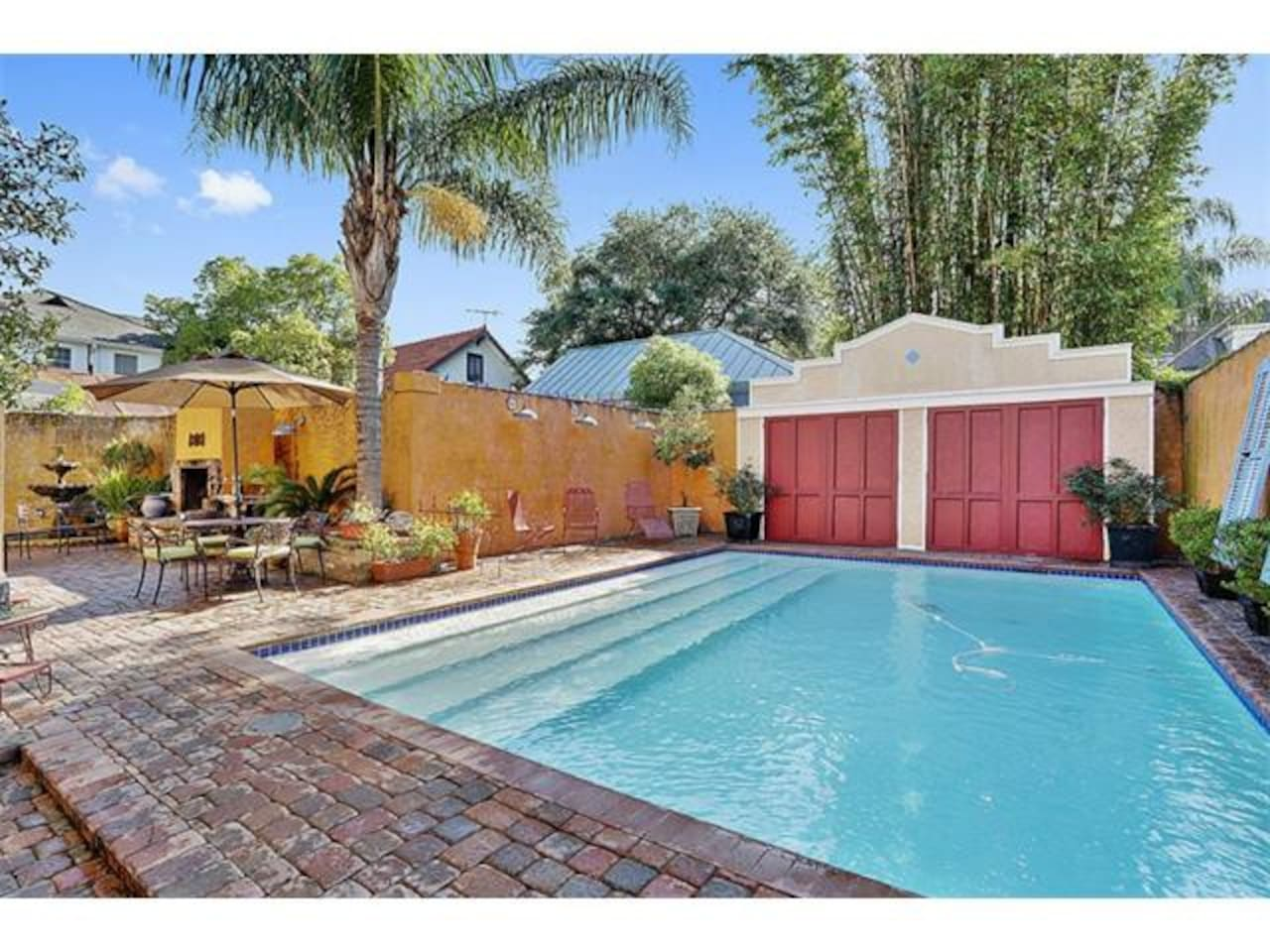 The backyard which features a pool, outdoor bathroom (including a shower) and an outdoor fireplace