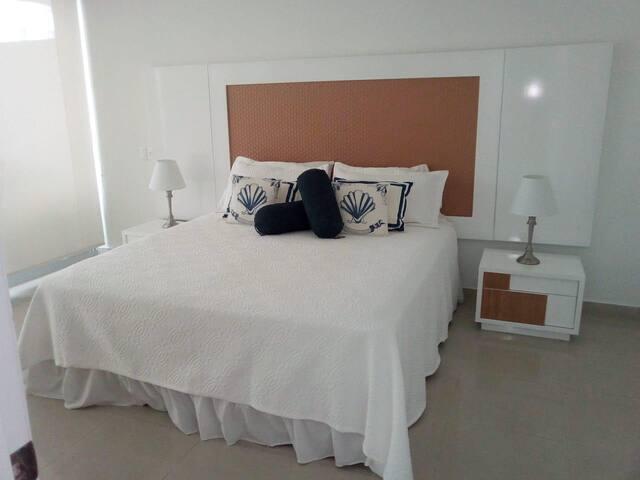 cuarto principal con cama King, aire acondicionado y TV y vestier interno