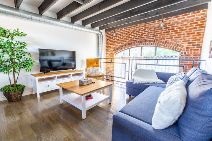 """(Living Room) Located on the duplex level of the loft. 50"""" Smart TV with access to local channels and apps like Netflix, HBO, Prime and more. Queen Size Sofa Bed with extra blankets and pillows. Beautiful window view of the neighborhood."""