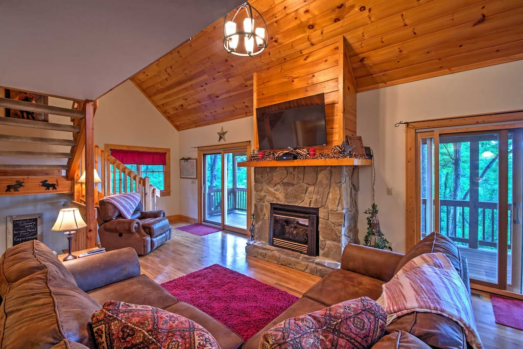 The living area features a stone propane insert fireplace, large flat-screen cable TV and a comfy wrap-around couch.