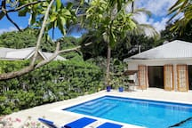 View of the sparkling pool, loungers and swing seat.  Pool Studio opens onto the deck.  The Cottage can be seen through the hedge.
