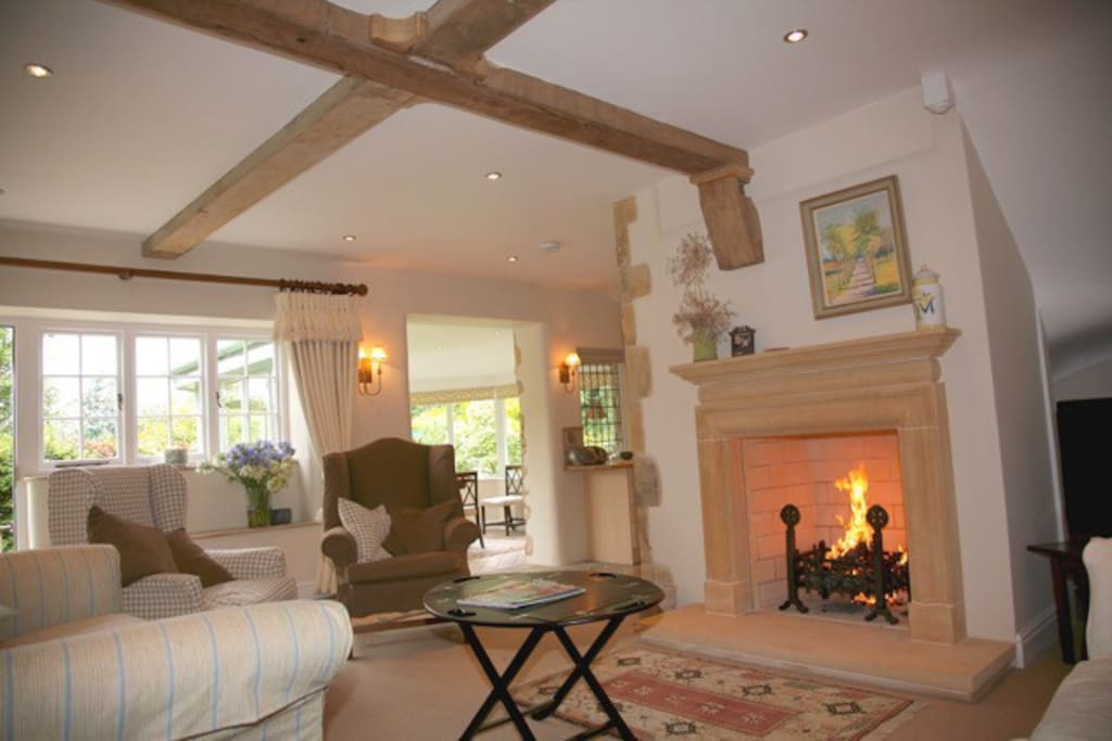 Sitting room - 2 sofas arm chairs open log fire - through to dining room conservatory-  ( fireguard available )