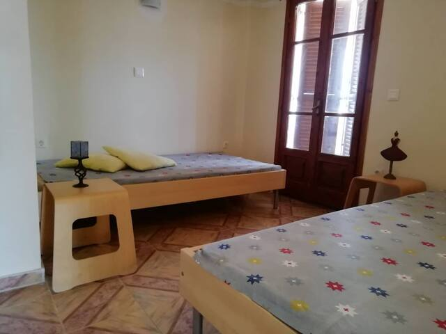 Bedroom provided with two beds. Balcony with a view towards the village.  Υπνοδωμάτιο με δύο   κρεβάτια. Μπαλκόνι προς το χωριό.