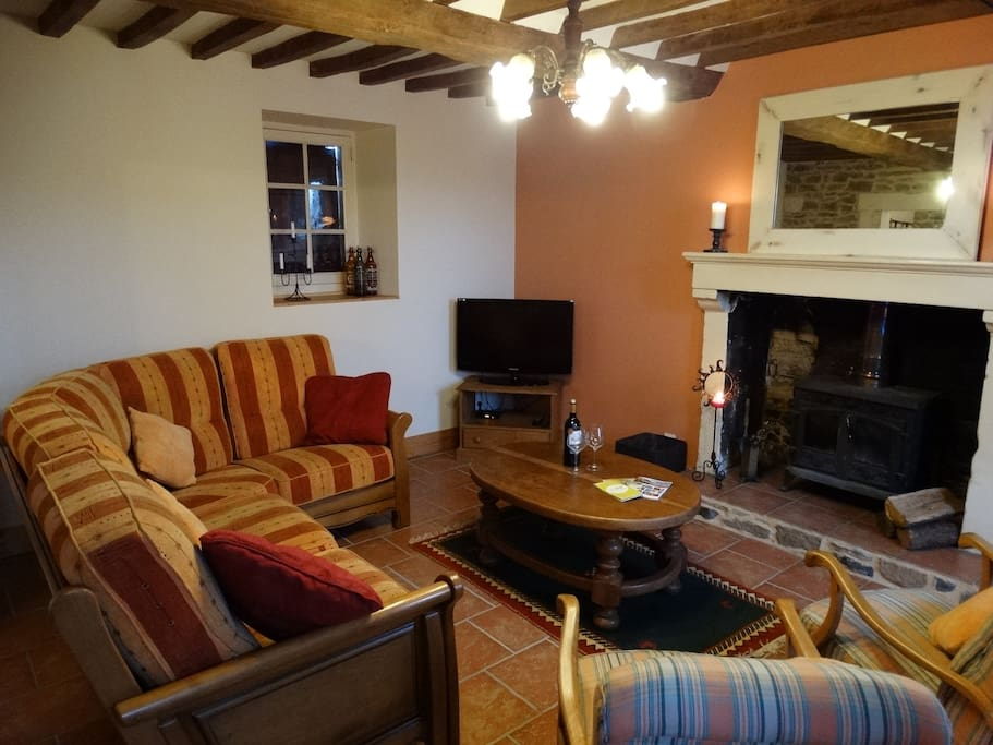 Living room with wood burning stove and beamed ceiling