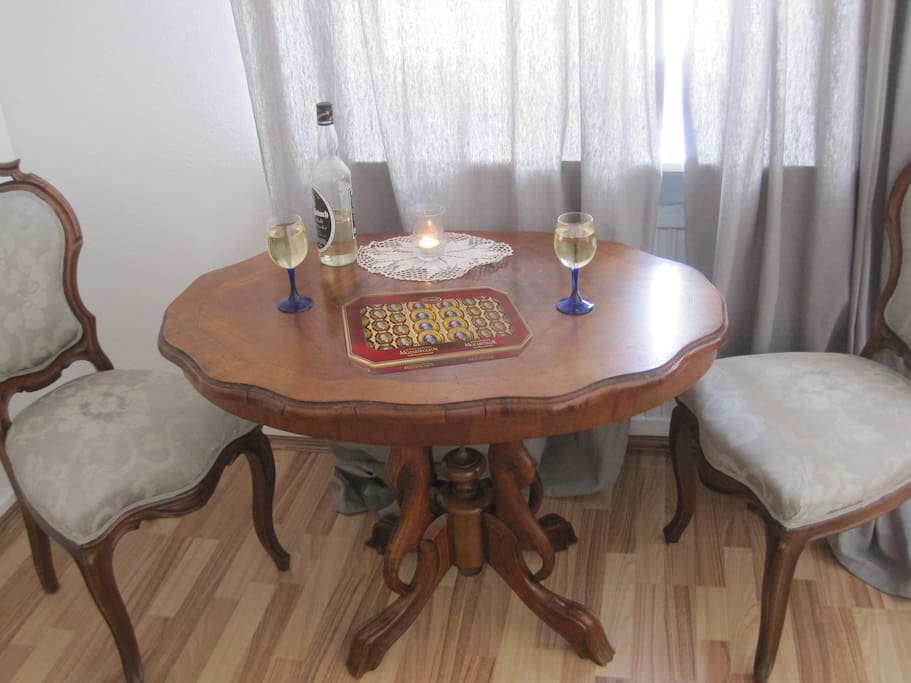 Master Bedroom with two large windows. Antique table and chairs