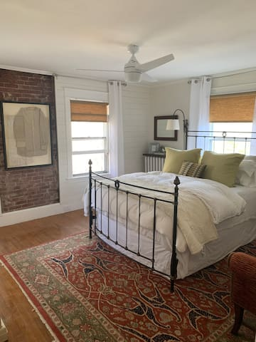 This guest bedroom is newly renovated and offers a queen bed, overhead fan, and air conditioning.  The art hanging on the brick is clothing that belonged to Patty's grandmother & grandfather.