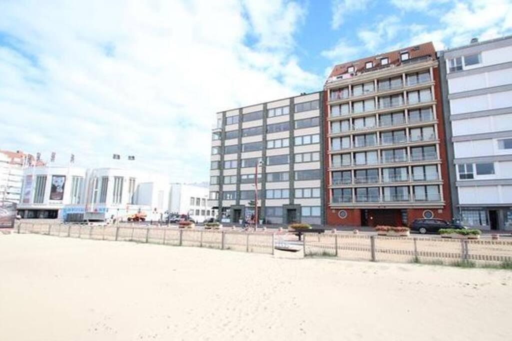 Vanaf strand gezien, in winter zonder de strandhuisjes. Het appartement nr 7-3 bevindt zich op de 7e verdieping, 3e van links, in het rode gebouw.