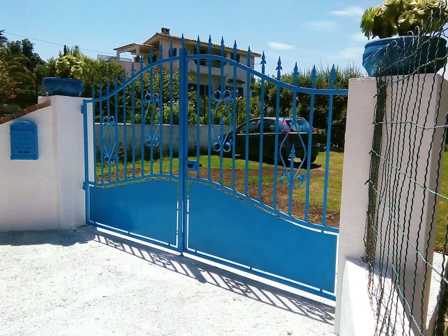 Cancello d'ingresso con vista parcheggio e casa sullo sfondo