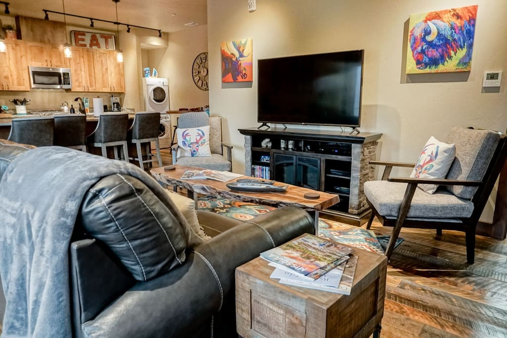 Large flatscreen TV in living room with cozy seating for all.