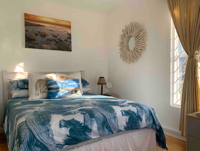 This 2nd bedroom gets the north facing afternoon sun, perfect for those who like to sleep in. It has a double bed plus a single bed, bar fridge, coffee station and tv with Netflix and Showmax.