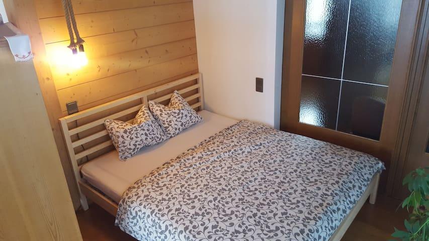 Bett im Wohnzimmer; abgetrennt durch Schiebtür (zum Esszimmer)