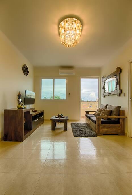 Sala climatizada con TV y balcón con vista al mar y la ciudad.