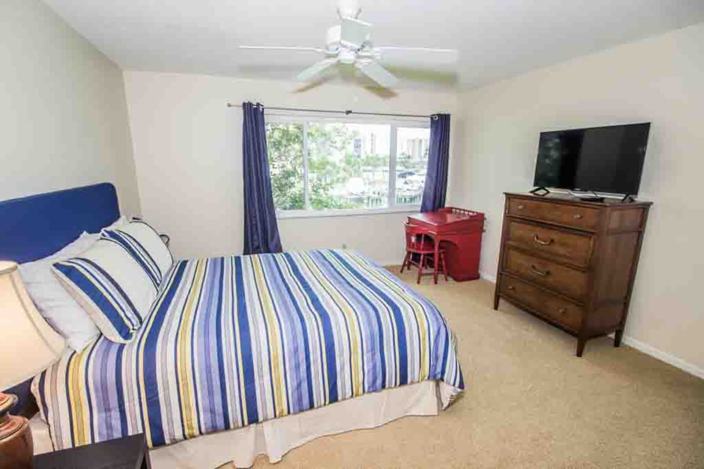 "Master bedroom with water view and 39"" smart TV"
