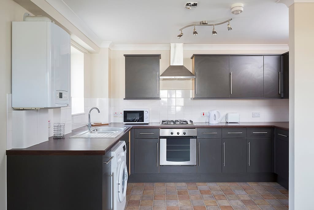 Modern kitchen with fridge, cooker, washing machine, microwave, kettle and toaster, plates, pots and pans, glasses, mugs and cutlery