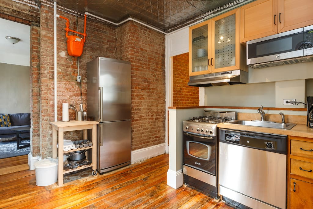 View of kitchen towards living space featuring original exposed brick.