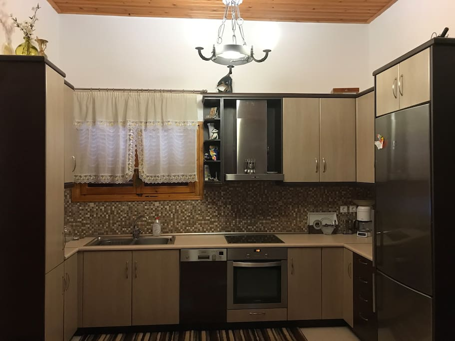 Full kitchen with large refrigerator and dishwasher. Stocked with plates and silverware.