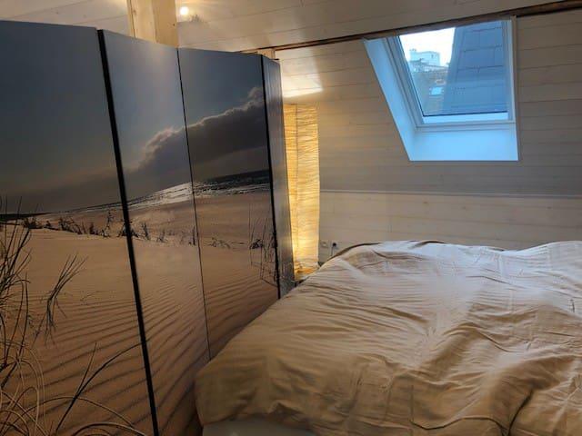 lit double, séparé du reste du loft par un paravent, qu'o peut aussi plier si on préfère.