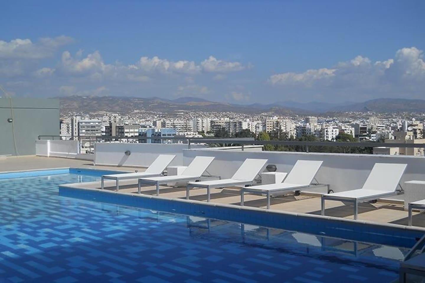 Rooftop pool with deck chairs, BBQ and entertaining area with ocean and mountain views