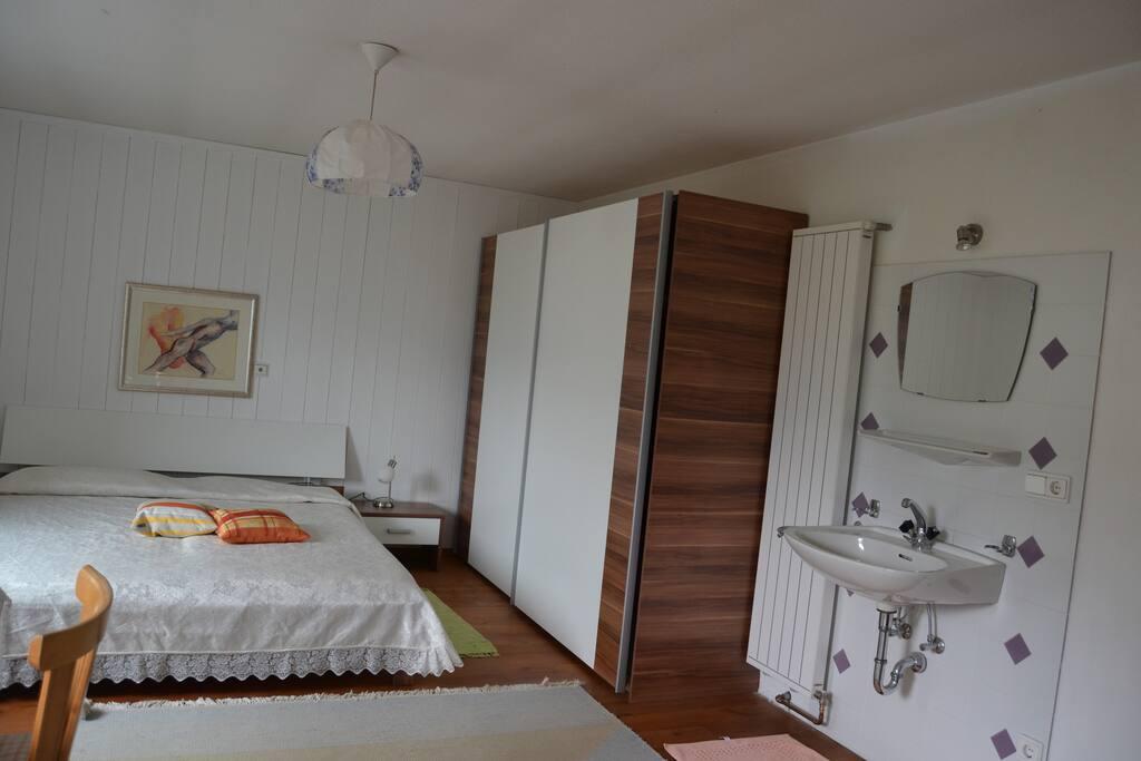 eines der beiden Schlafzimmer, mit Doppelbett und Waschbecken im Zimmer, Zustellbett(en) möglich