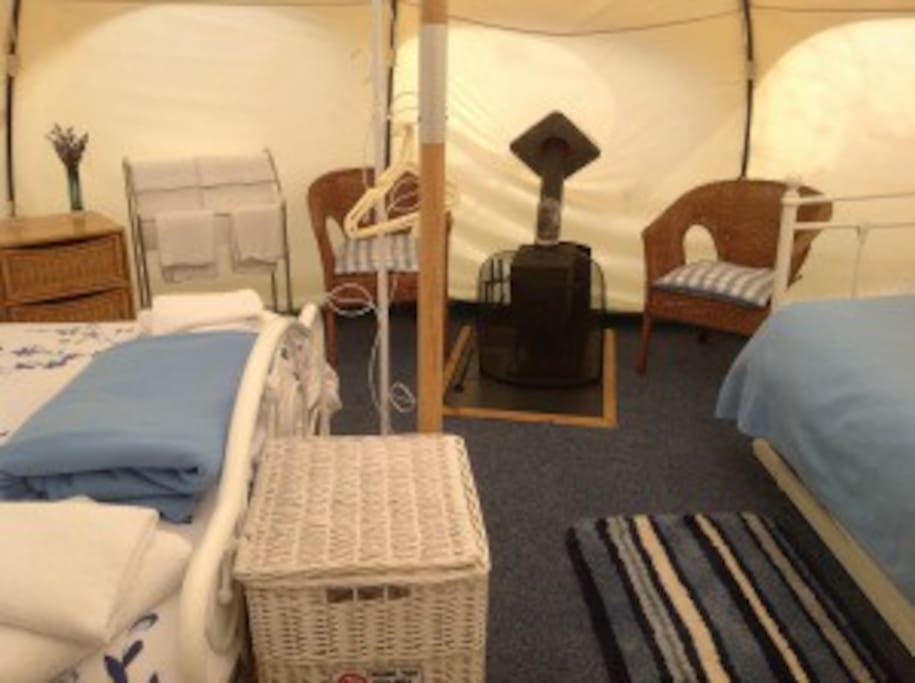 Inside Bluebell tent, double bed on the left, edge of day bed on the right and log burner in the middle.