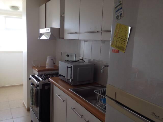Cocina completamente equipada que cuenta con microondas hervidor refrigerador cocina ollas cuchilleria