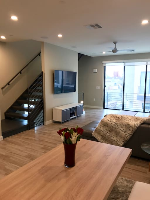Sit at the kitchen table while watching TV on our 65 in. smart TV - full cable included! Need to unwind? Walk up the stairs to the bedrooms!