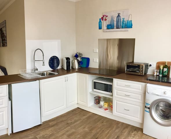 Kitchen with all the amenities, coffee machine, cooktop, toaster oven, fridge, washer,