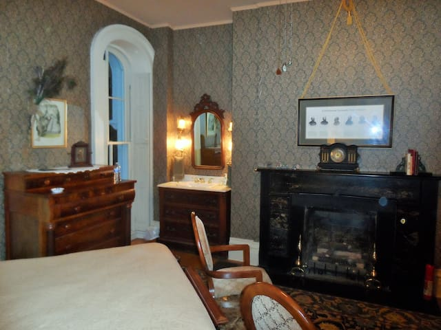 Generals Room showing Antique Sink with Mirror, Hand Towels, Wash Cloths, Luxury Toiletries, and Hair Dryer adjacent to Fireplace
