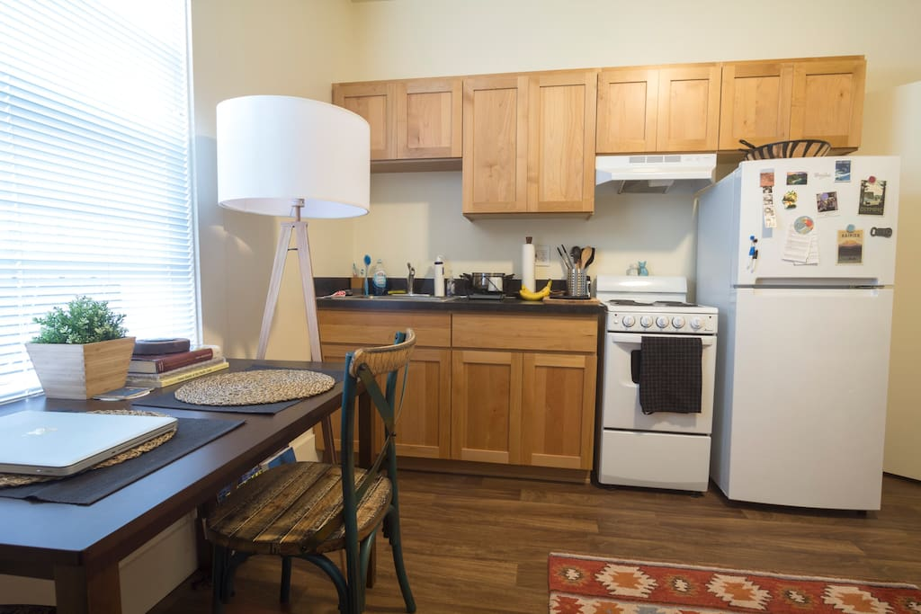 The kitchen section includes a refrigerator, stove, oven, and cabinets to store items.