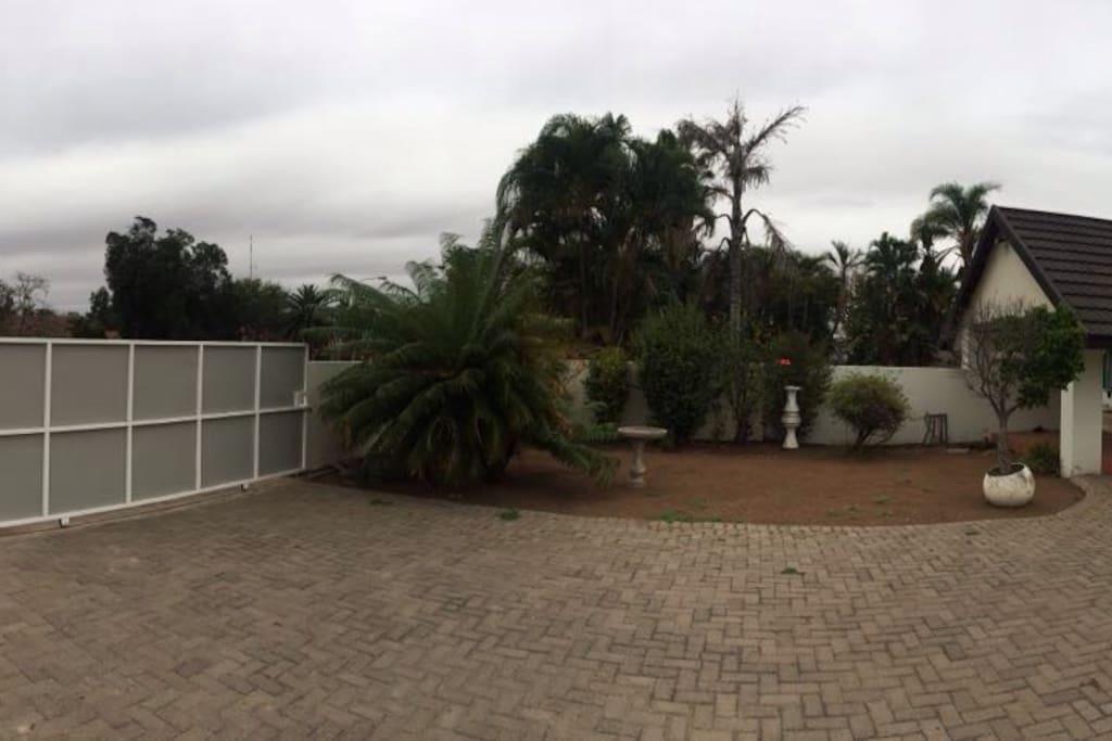 Het terras met  rechts de woning en links de toegangspoort