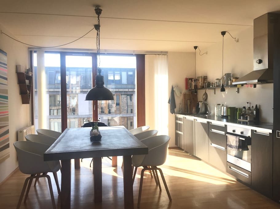 Bright dining area with an open kitchen and a dining table for 8 people.