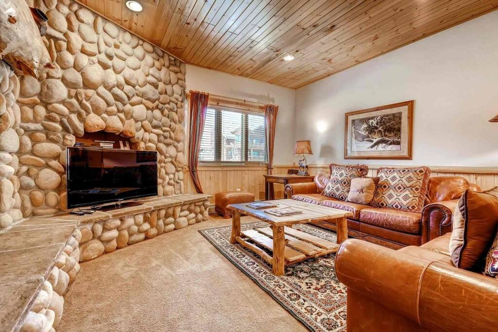 """Living area offers a large 48"""" HDTV, comfortable high end leather furniture, mountain decor and detailing and a floor to ceiling river rock fireplace."""