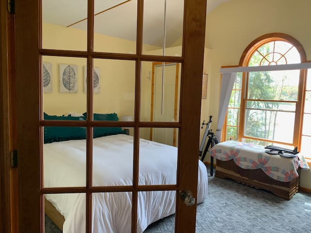 Upstairs bedroom with queen bed, closet, and great view of the lake.