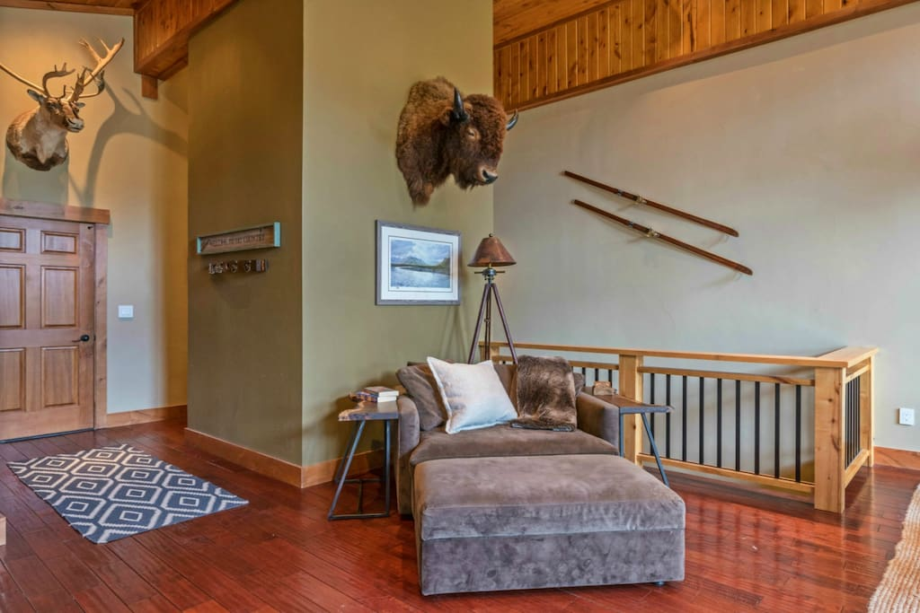 Comfy reading loveseat under bison & caribou mounts and Peter Corbin artwork