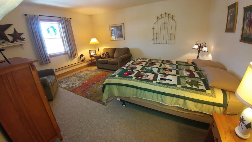 Spacious bedroom offers a queen bed, loveseat, recliner and chest of drawers.
