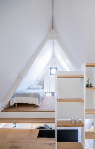 La petite chambre en mezzanine, ouverte sur l'appartement