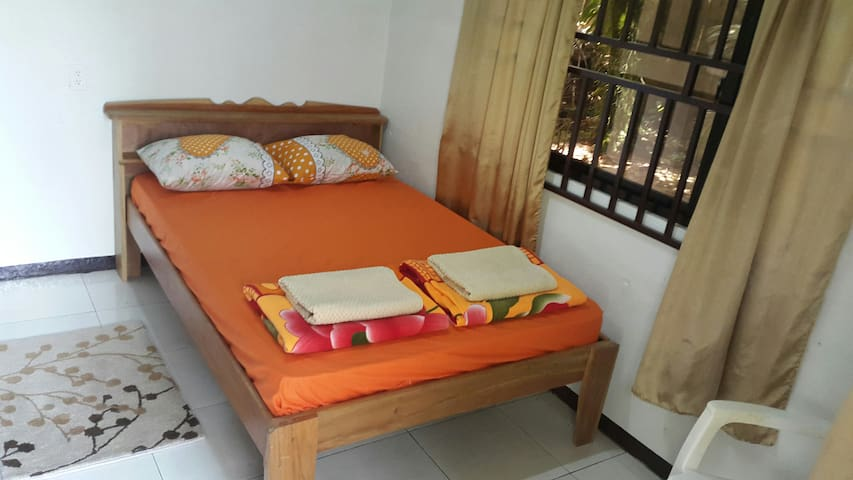 Double bed with inner spring mattress. View from window to the backyard.